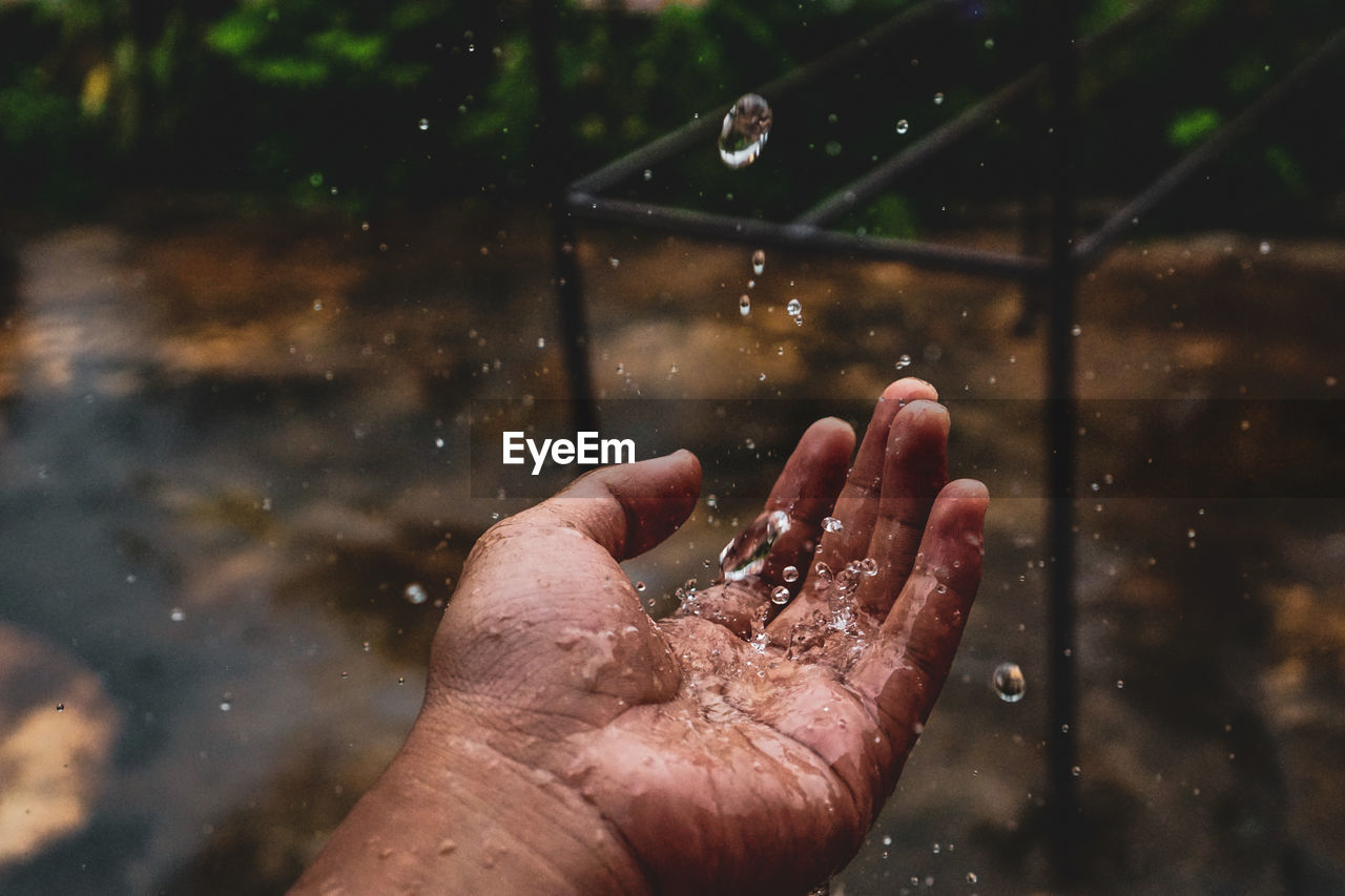 Close-up of hand catching water during rainy season