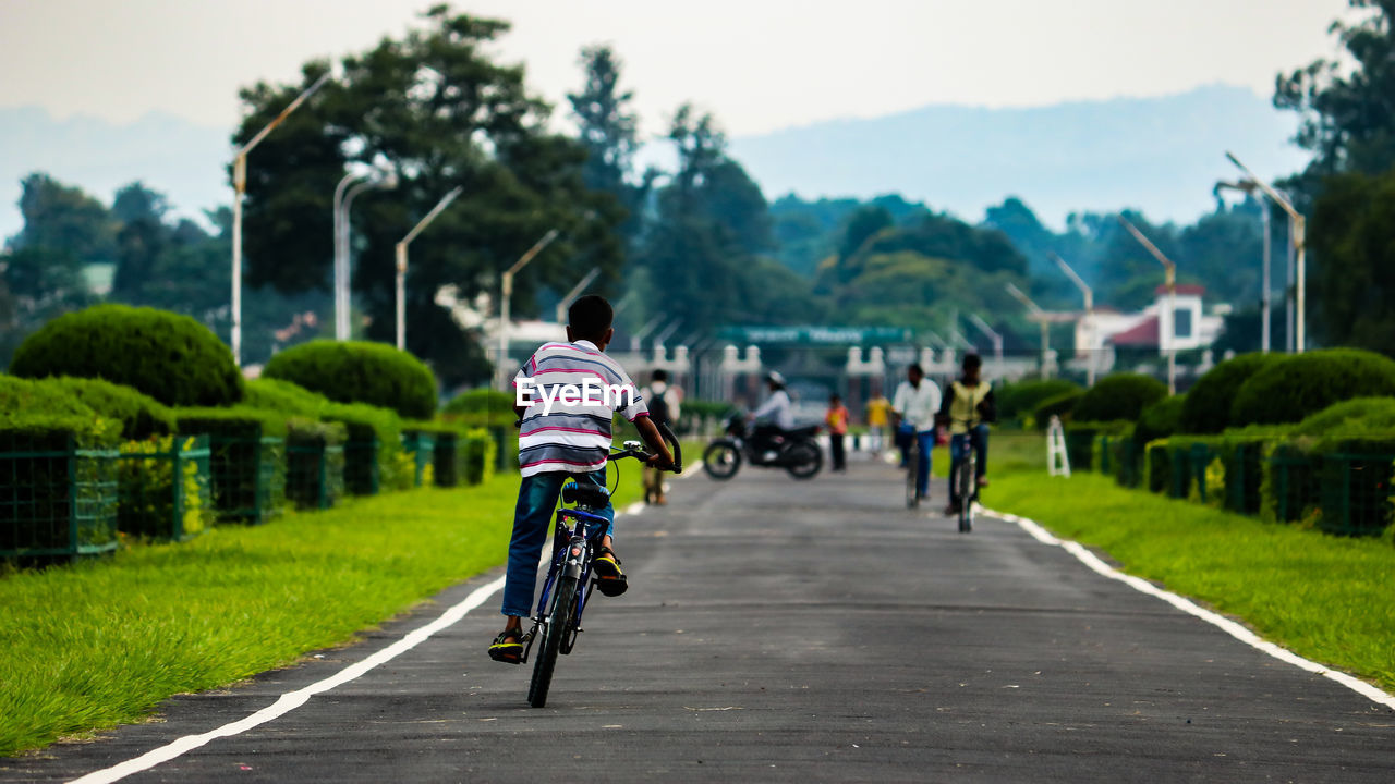 transportation, bicycle, real people, rear view, lifestyles, sport, people, land vehicle, road, activity, the way forward, men, cycling, mode of transportation, ride, riding, plant, leisure activity, full length, focus on foreground, outdoors