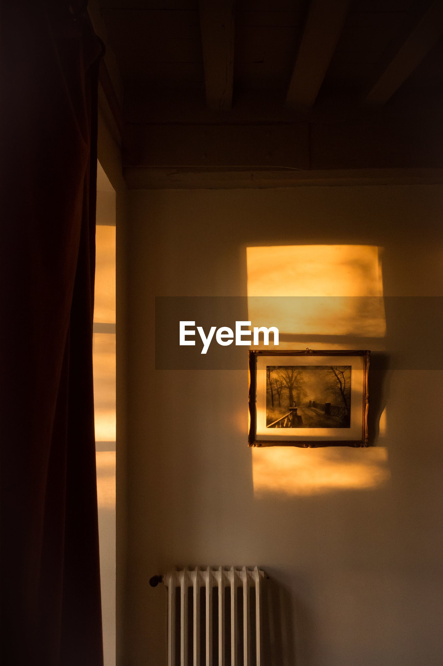 indoors, no people, architecture, illuminated, built structure, window, sunset, wall - building feature, low angle view, sunlight, nature, technology, lighting equipment, absence, wood - material, domestic room, close-up, orange color, ceiling