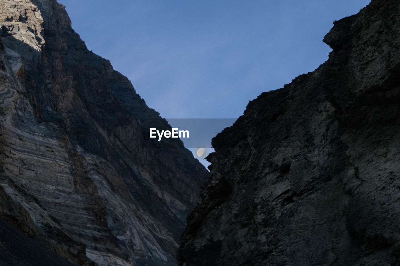 sky, rock, low angle view, mountain, nature, mountain range, beauty in nature, tranquility, clear sky, day, no people, rock formation, rock - object, formation, solid, tranquil scene, scenics - nature, outdoors, rocky mountains, non-urban scene, mountain peak, eroded