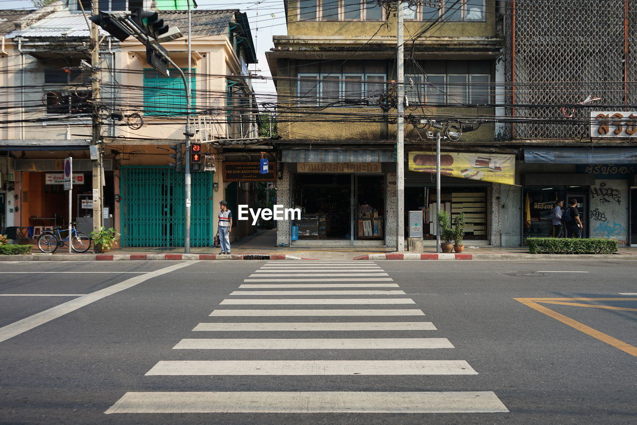 road marking, built structure, architecture, road, sign, symbol, marking, city, building exterior, transportation, crosswalk, street, zebra crossing, crossing, day, direction, the way forward, outdoors, building, no people, dividing line