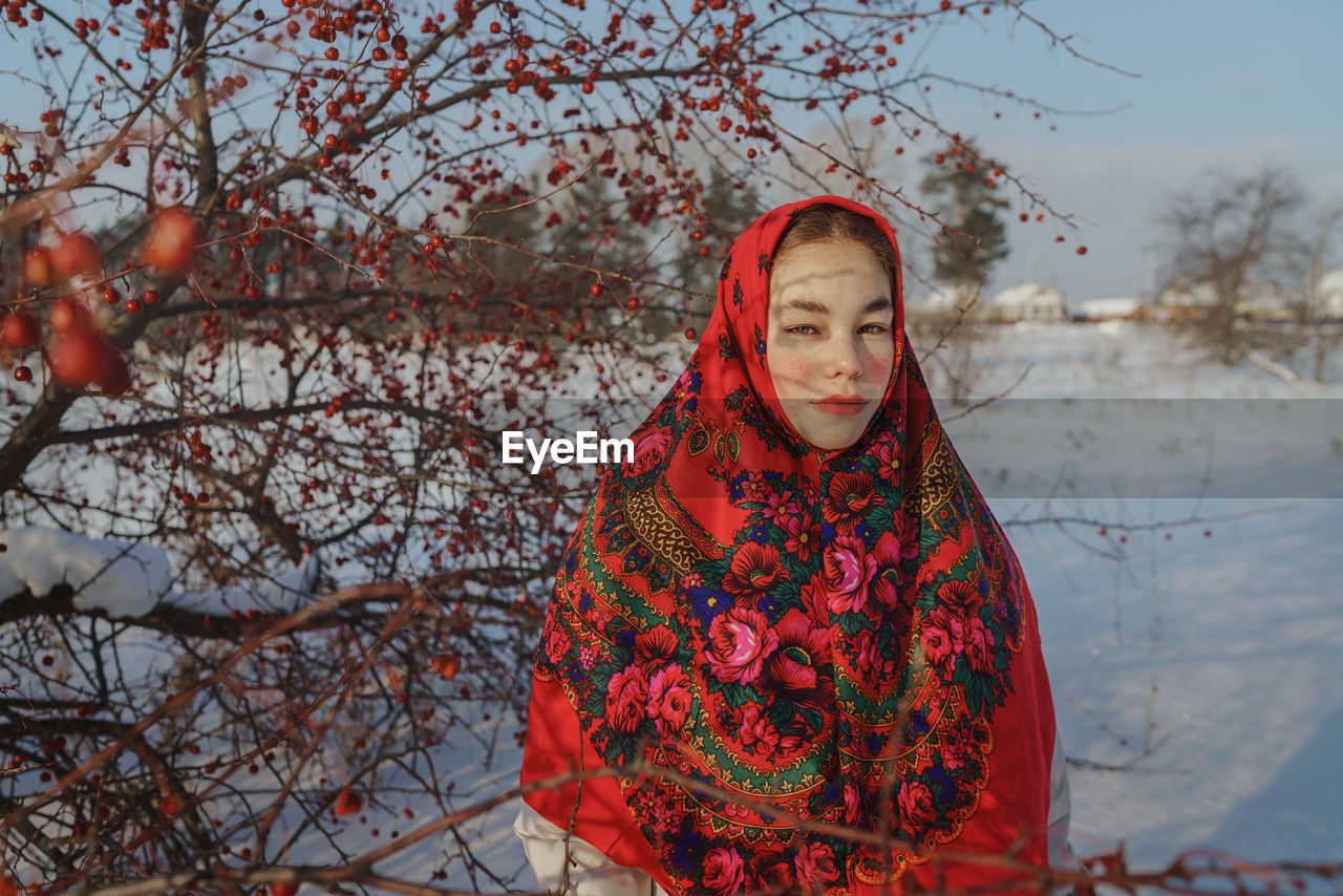 Woman standing by tree during winter in red shawl