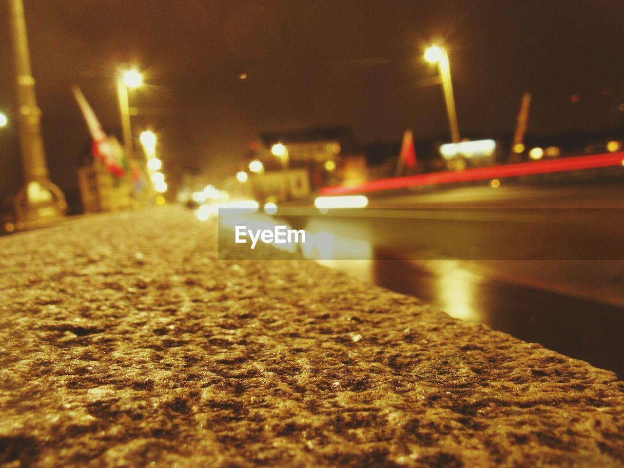 Surface Level Of Sidewalk Against Illuminated Street At Night