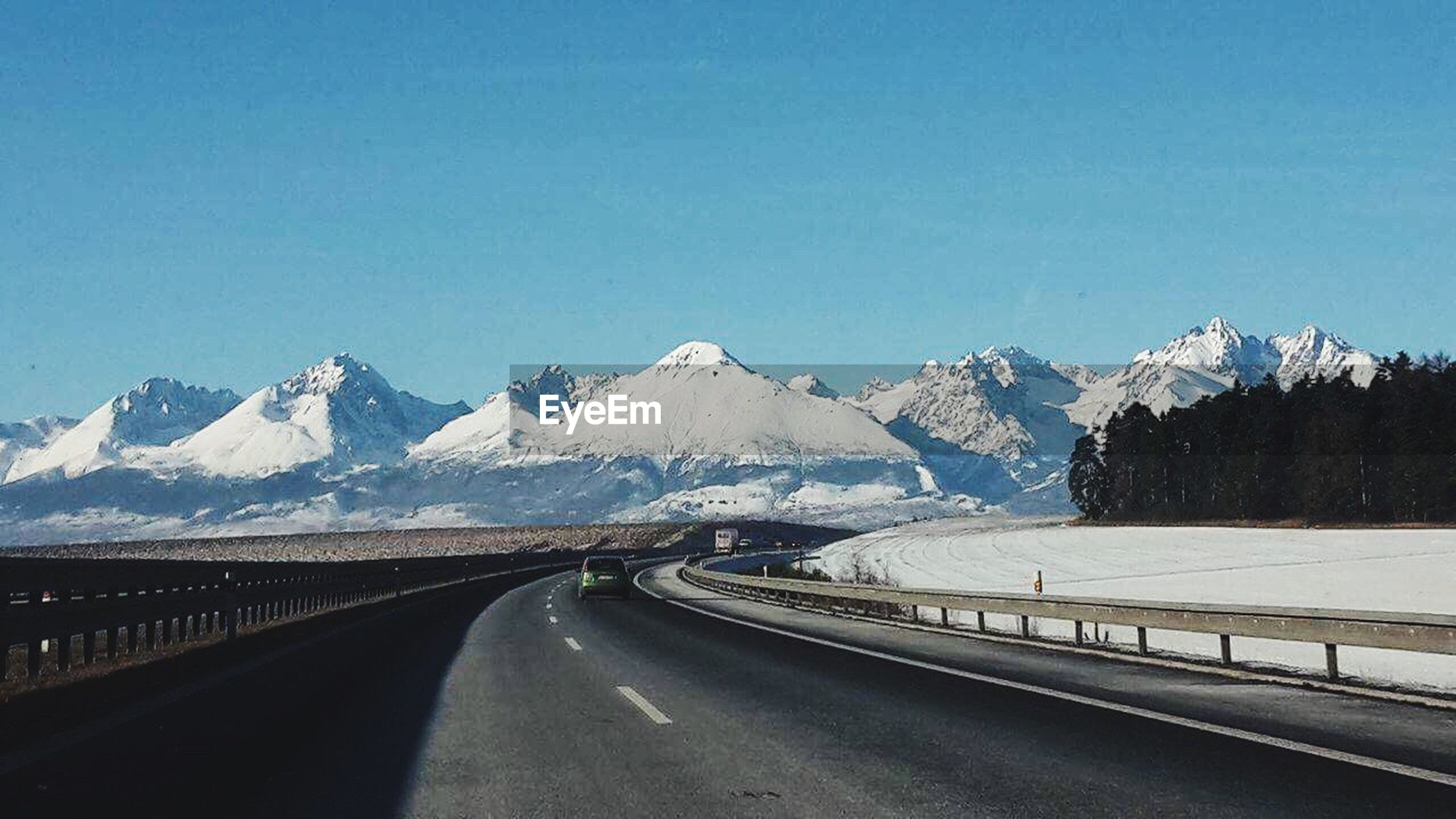 mountain, road, mountain range, the way forward, blue, landscape, snow, cold temperature, scenics, transportation, beauty in nature, clear sky, curve, idyllic, nature, outdoors, winter, day, no people, winding road