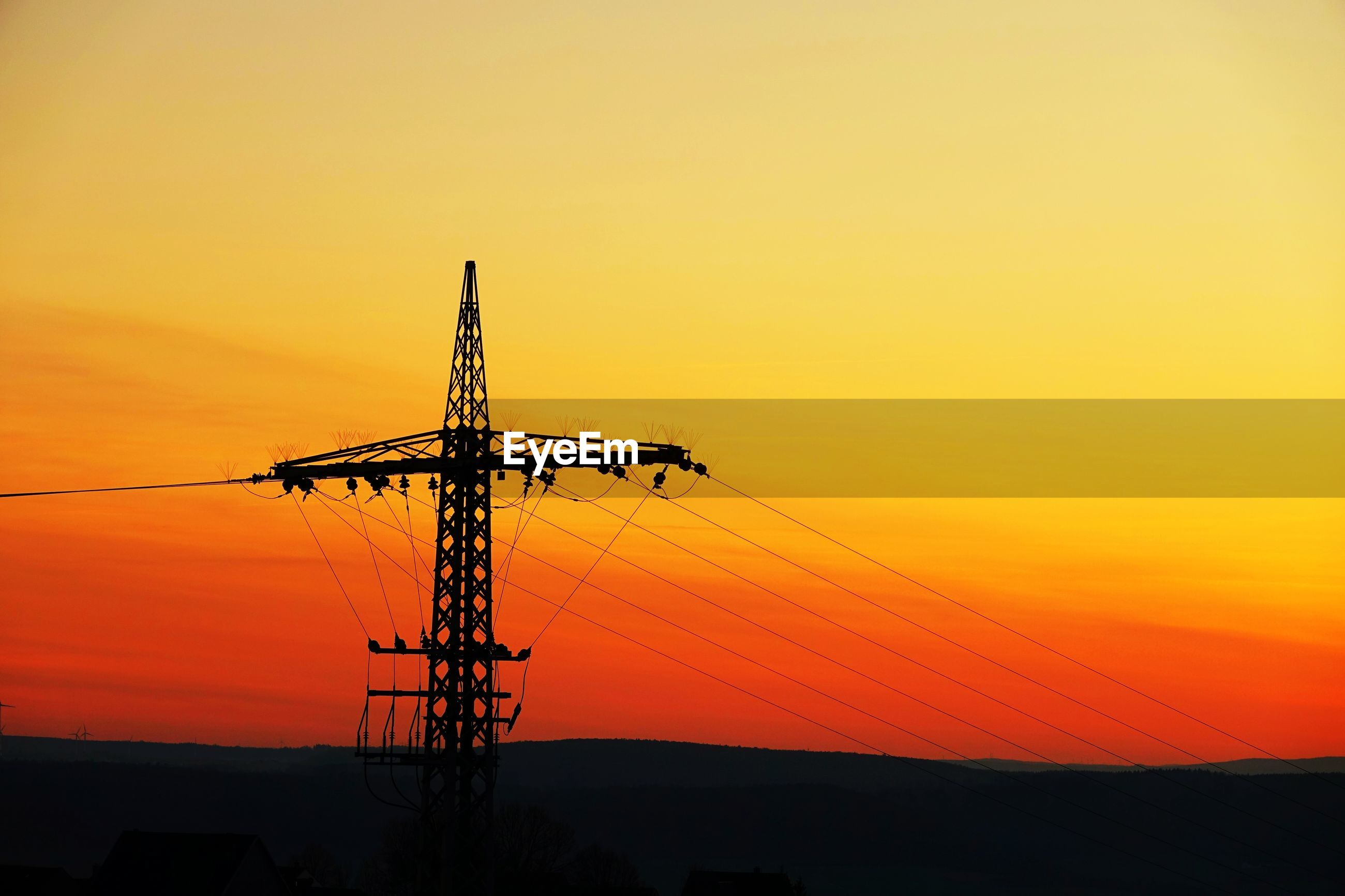 SILHOUETTE OF ELECTRICITY PYLON AGAINST ROMANTIC SKY AT SUNSET
