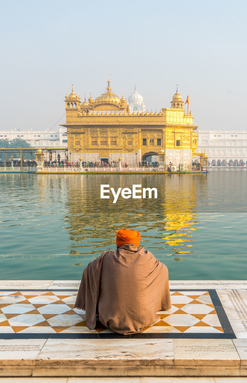 Rear view of man praying against golden temple amidst standing water