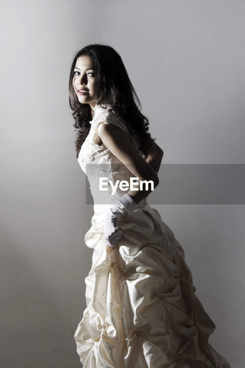 Portrait of bride standing against gray background