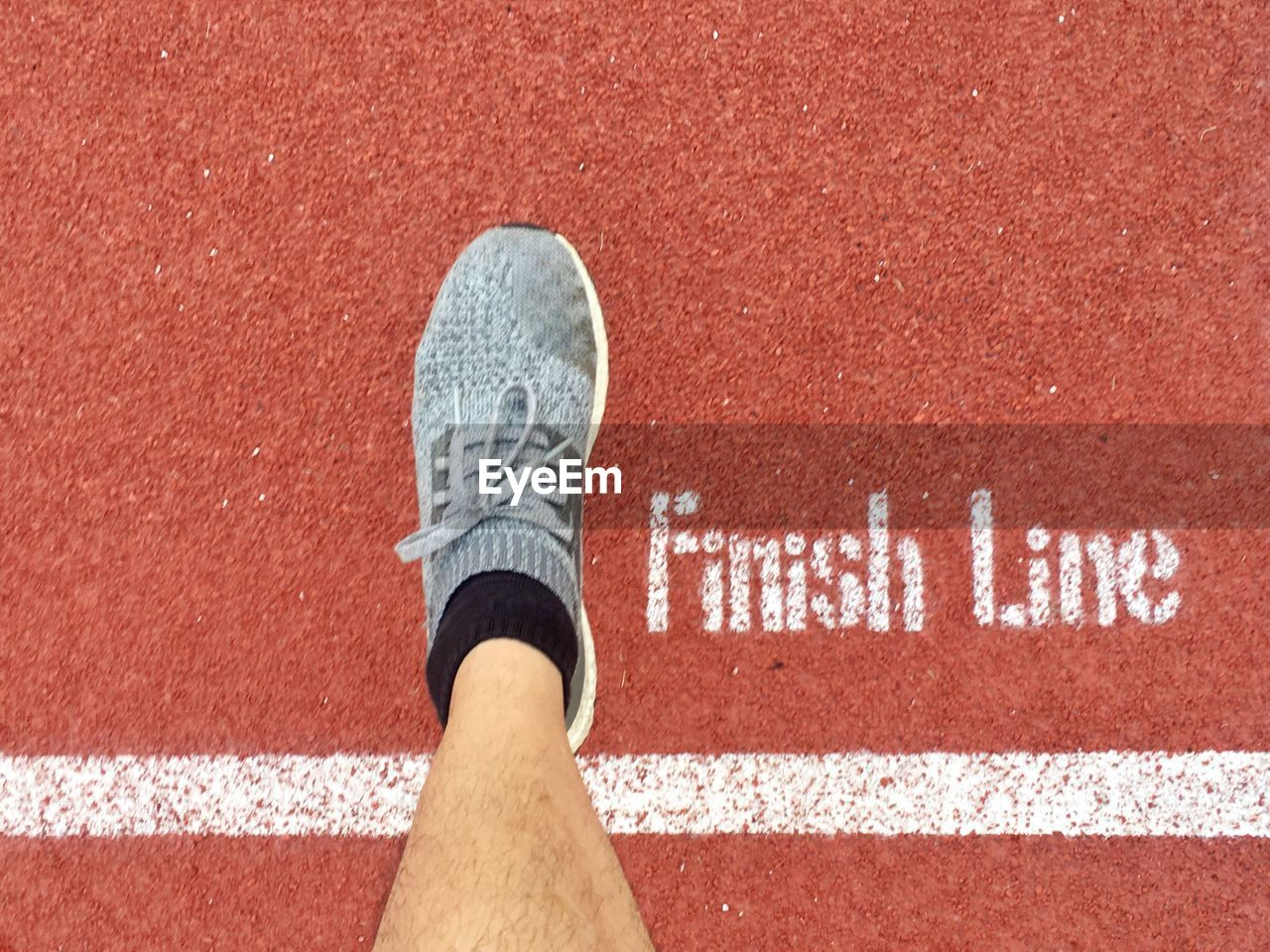 sport, running track, track and field, human body part, one person, body part, shoe, human leg, low section, day, competition, sports shoe, limb, starting line, standing, red, track event, sign, running, human limb, human foot, dividing line