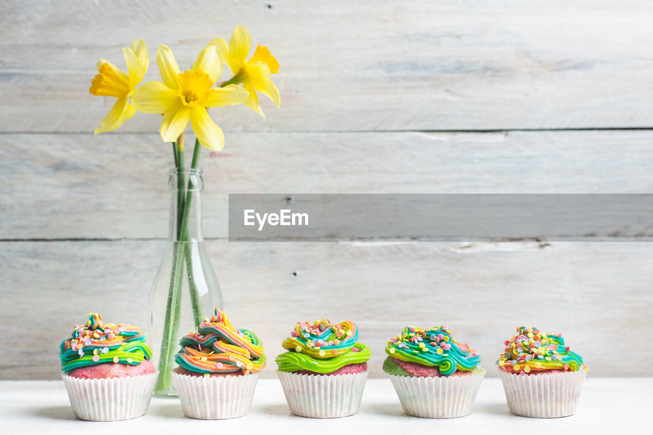 flowering plant, flower, freshness, sweet food, cake, sweet, dessert, plant, table, cupcake, food, indulgence, multi colored, wood - material, no people, food and drink, baked, still life, nature, temptation, flower head