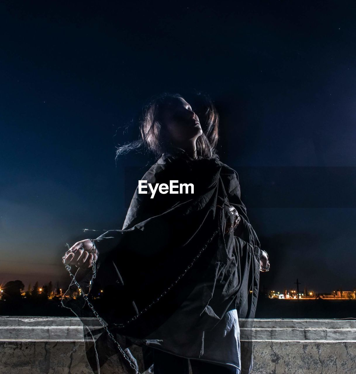 Double exposure image of woman holding chain against sky at night