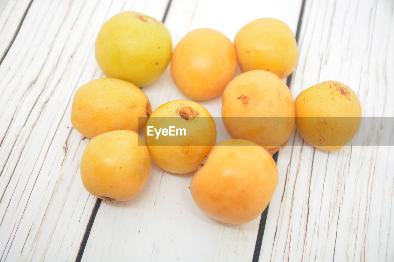 food and drink, table, freshness, food, still life, healthy eating, indoors, high angle view, fruit, wood - material, wellbeing, close-up, no people, group of objects, yellow, orange color, citrus fruit, orange - fruit, orange, day
