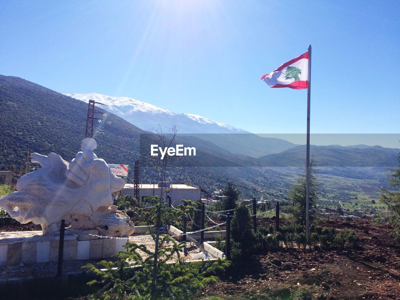 Lebanese Flag And Sculpture Against Mountains During Winter