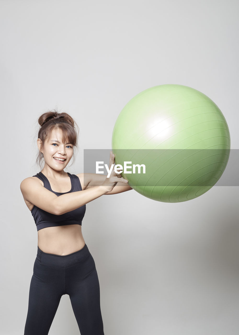 Woman Exercising With Green Fitness Ball Against White Background