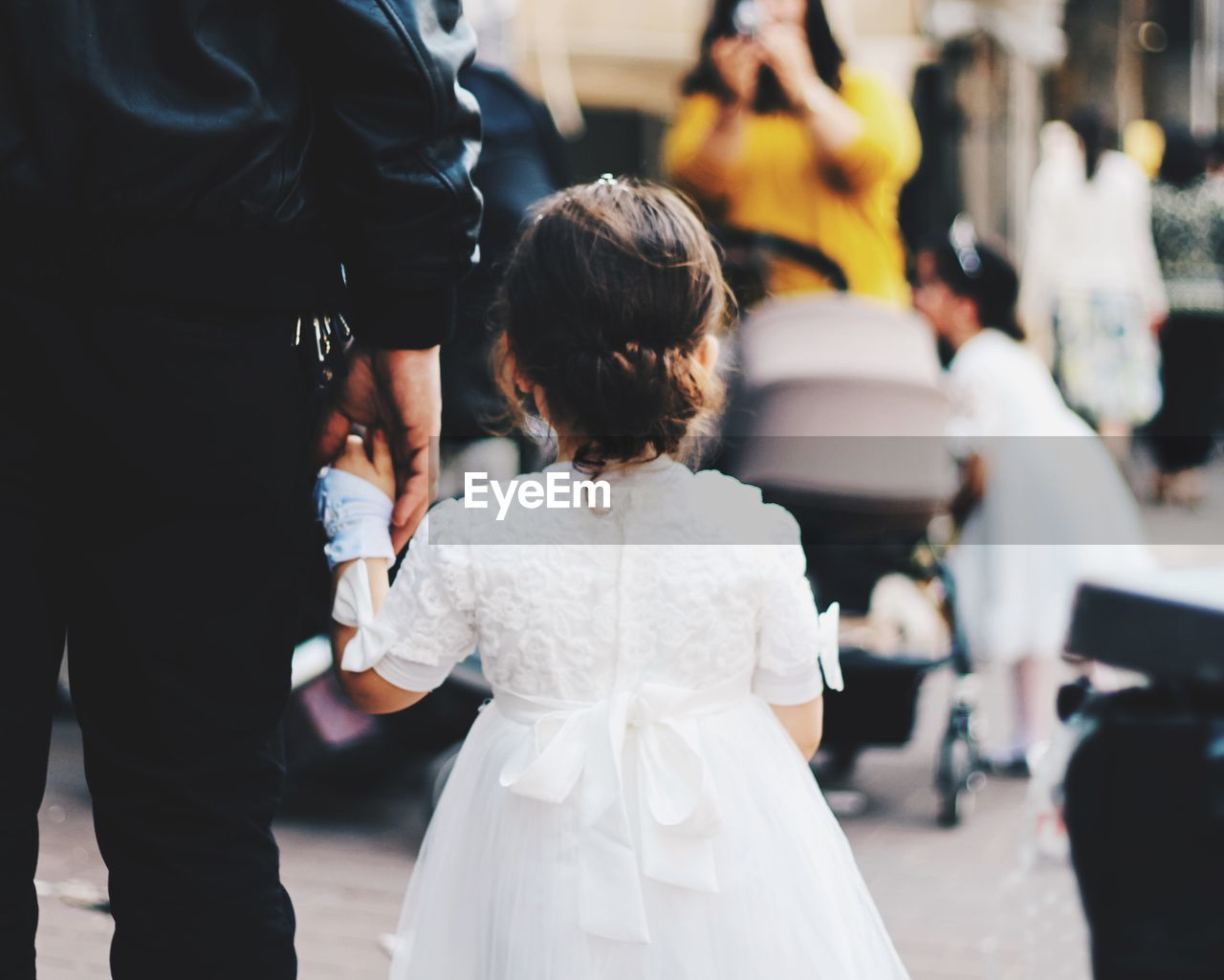 Rear View Of Girl In Costume While Standing With Father On Footpath