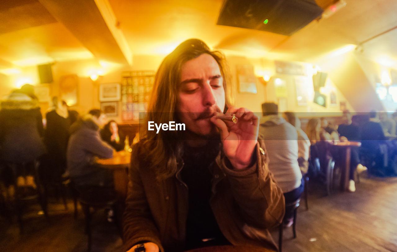 Young Man Smoking Marijuana Joint At Restaurant