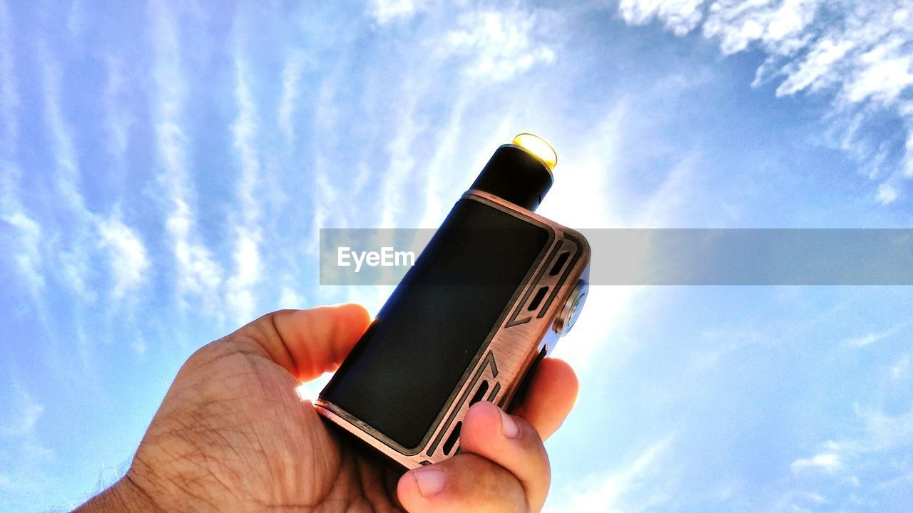 human hand, hand, holding, cloud - sky, sky, one person, human body part, real people, unrecognizable person, nature, low angle view, day, personal perspective, leisure activity, lifestyles, outdoors, body part, sunlight, communication, finger