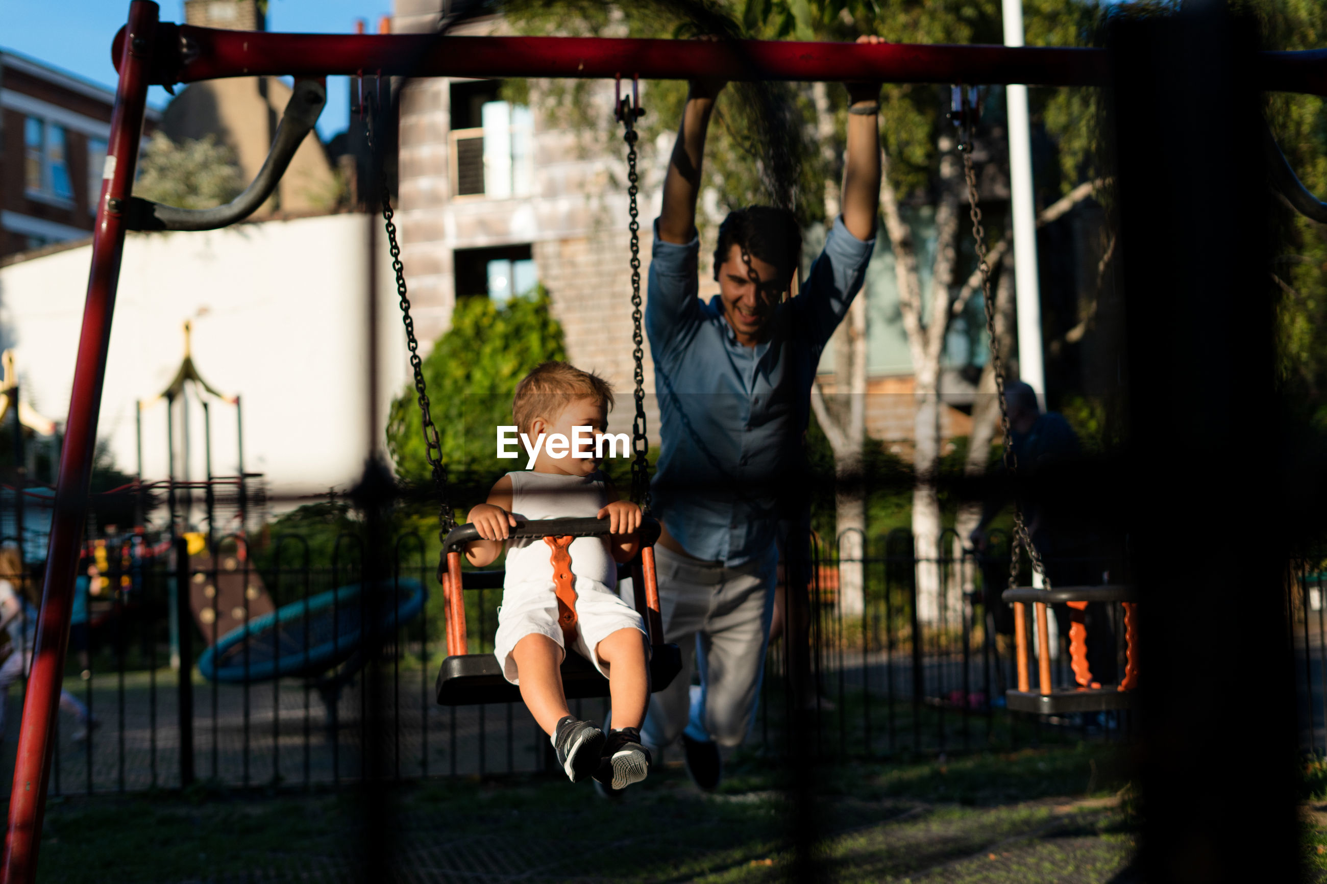 Girl with man swinging in playground