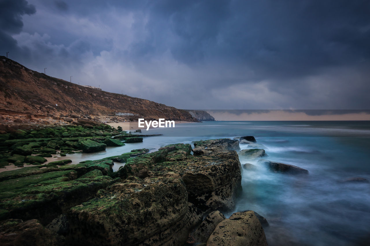Scenic View Of Rock Formations By Sea Against Cloudy Sky