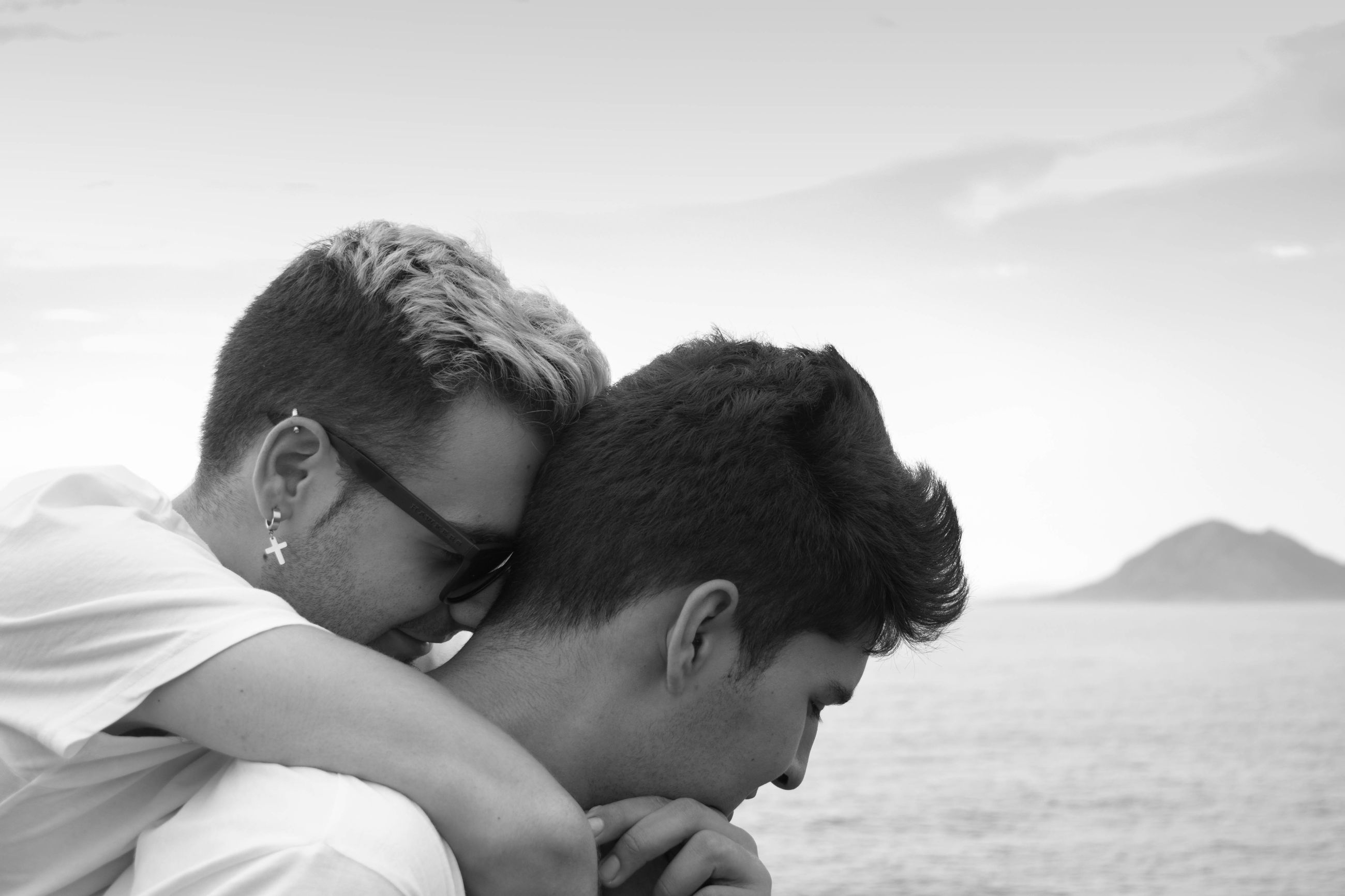 Close-up of homosexual couple embracing by sea against sky