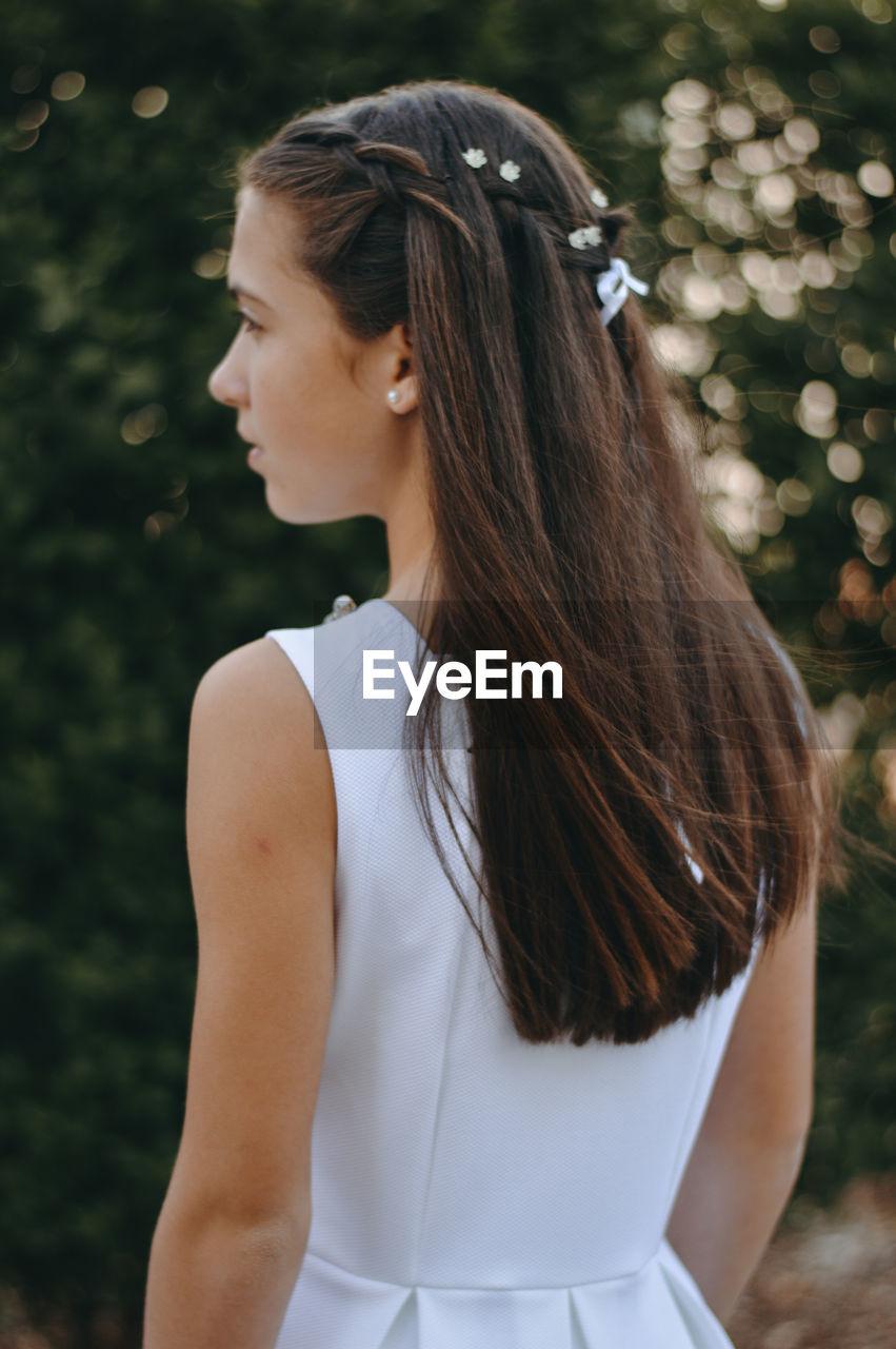 Teenage girl with long hair looking away
