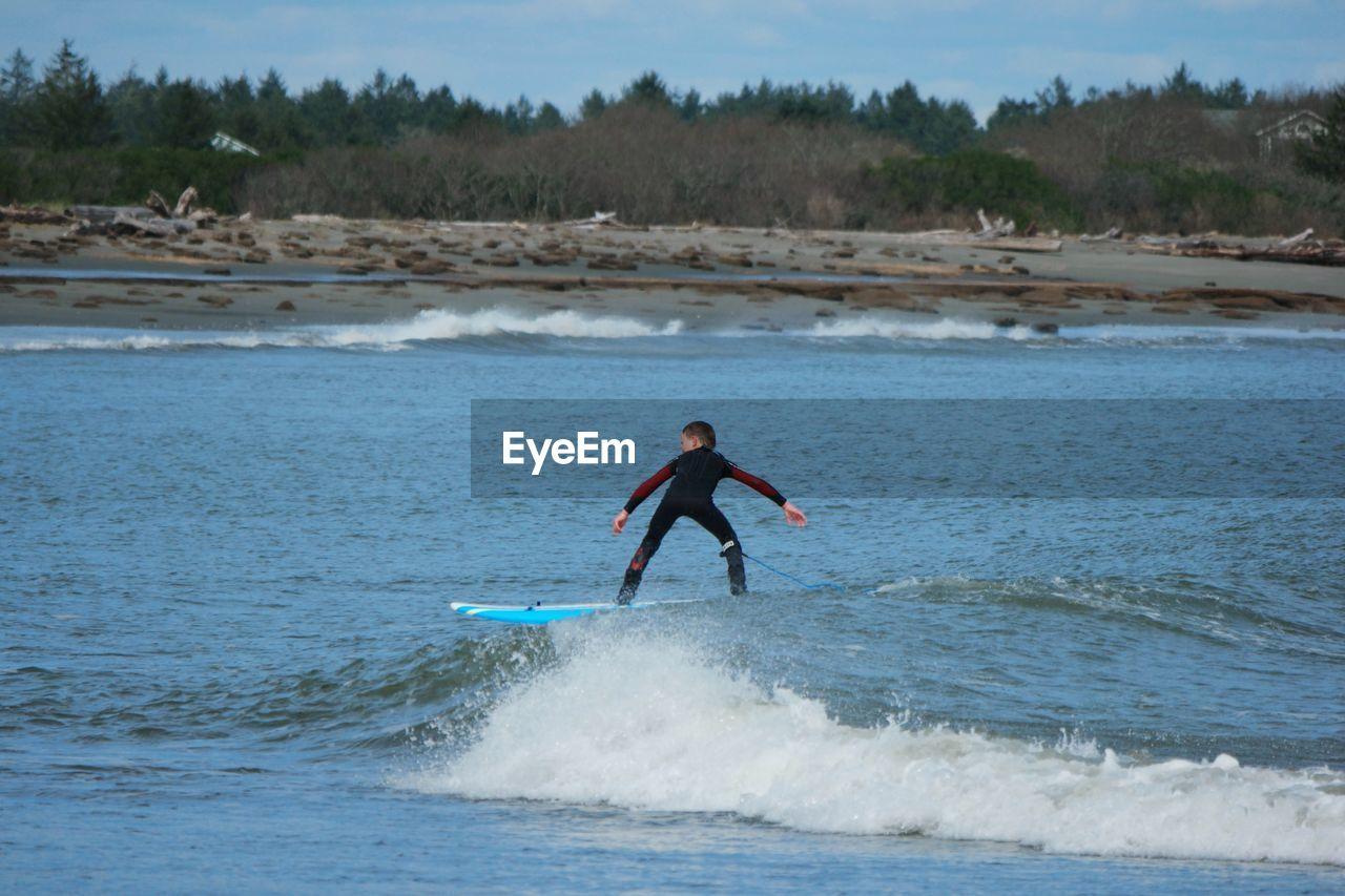 Rear view of boy surfboarding in sea