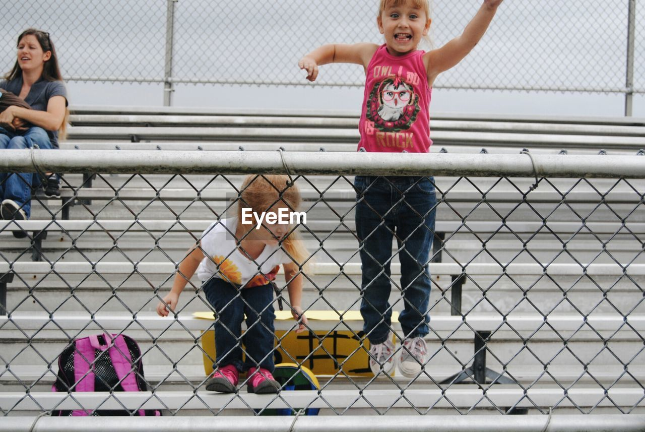 chainlink fence, childhood, full length, day, outdoors, togetherness, child, real people, girls, teamwork, sports team, people