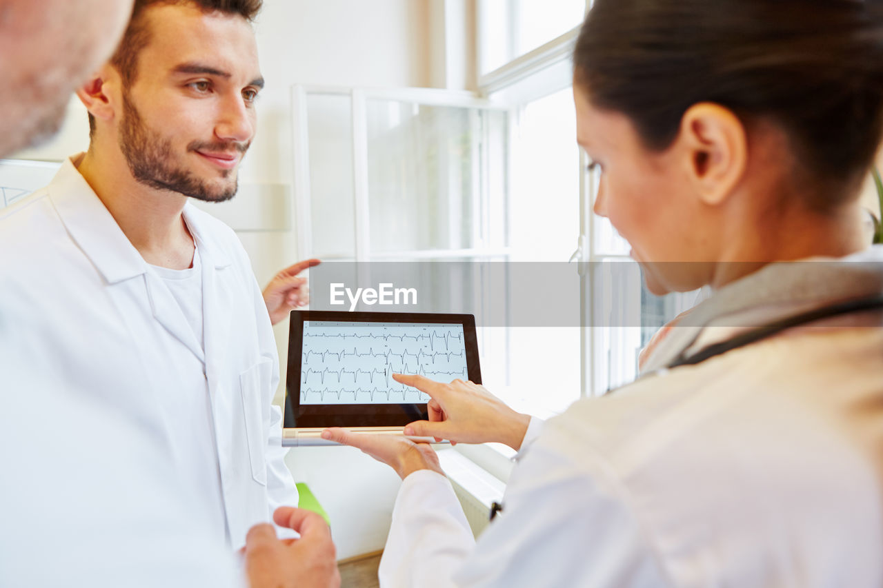 Smiling Doctor Using Digital Tablet By Colleague In Hospital