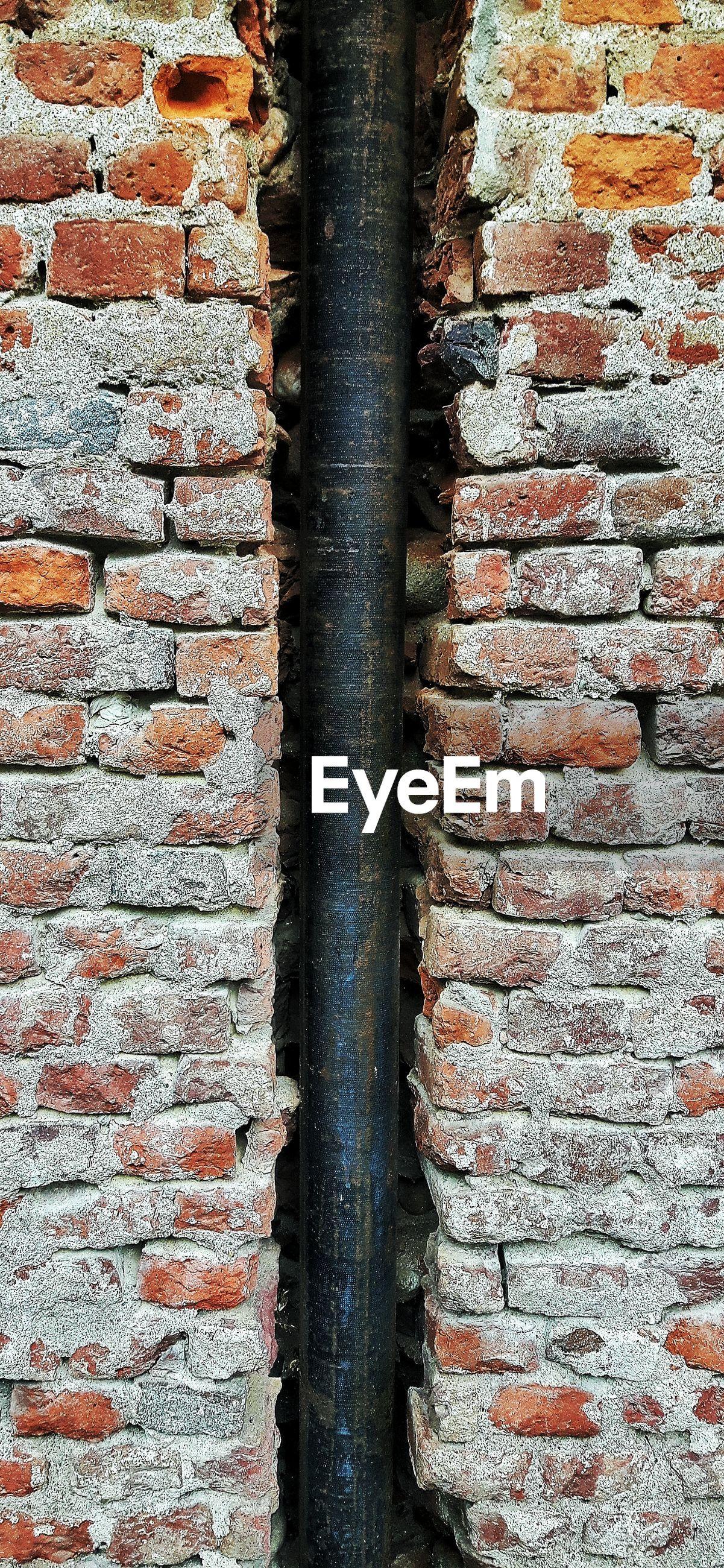 Pipeline amidst brick walls
