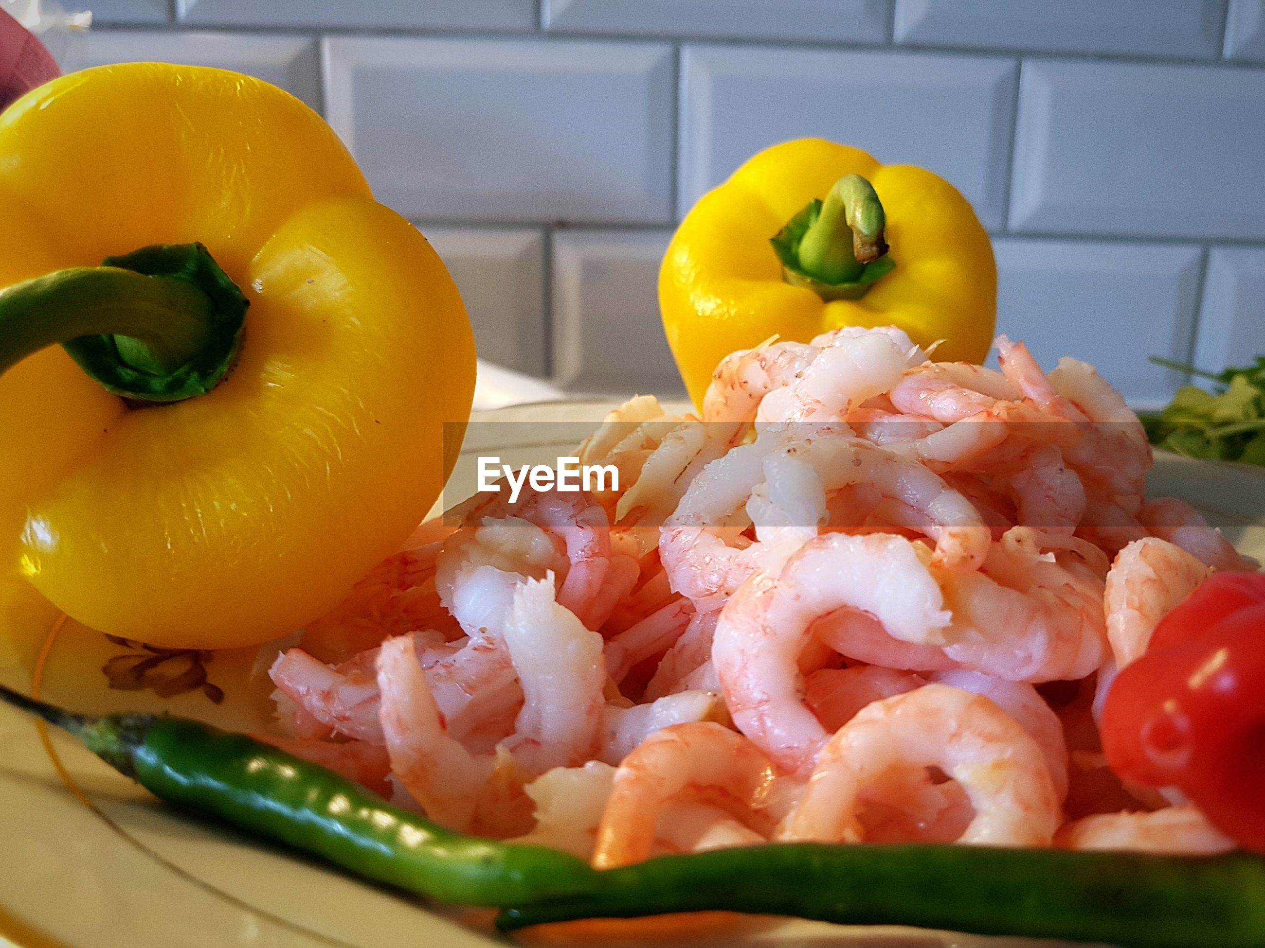 Close-up of bell peppers with prawns and chili peppers in plate