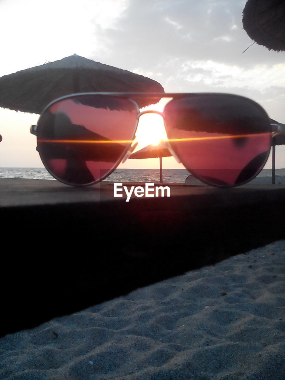 sunglasses, sunset, sky, nature, water, sunlight, outdoors, sea, tranquil scene, beauty in nature, beach, tranquility, sun, no people, scenics, sand, day, close-up