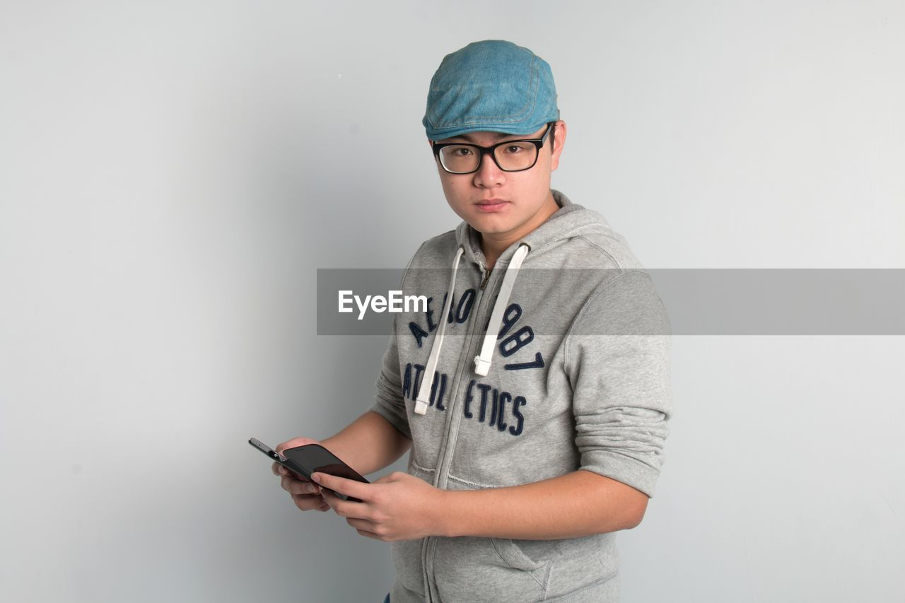 one person, casual clothing, wireless technology, mobile phone, glasses, communication, indoors, eyeglasses, holding, waist up, standing, front view, lifestyles, technology, smart phone, portrait, using phone, connection, teenager