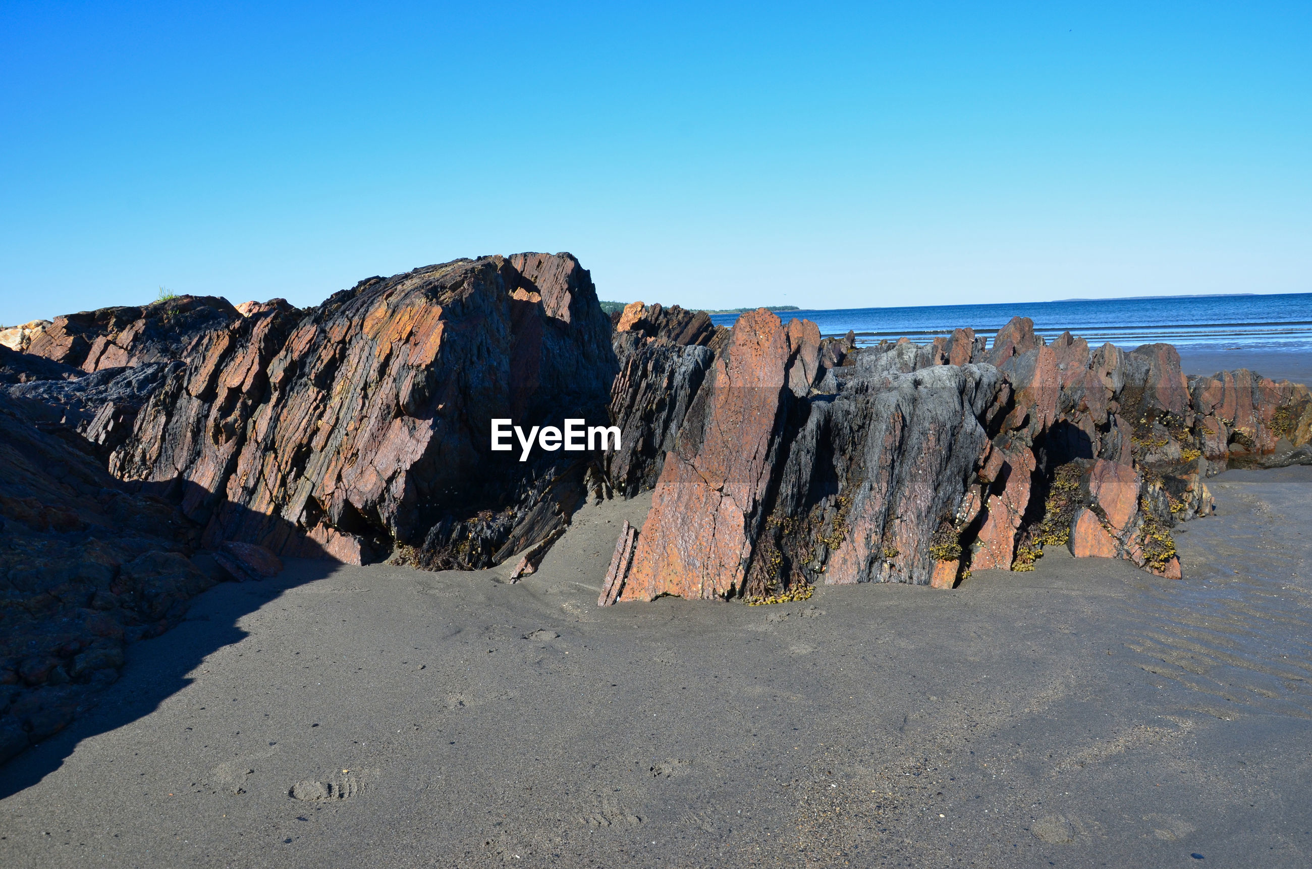 Panoramic view of rocks and sea against clear blue sky