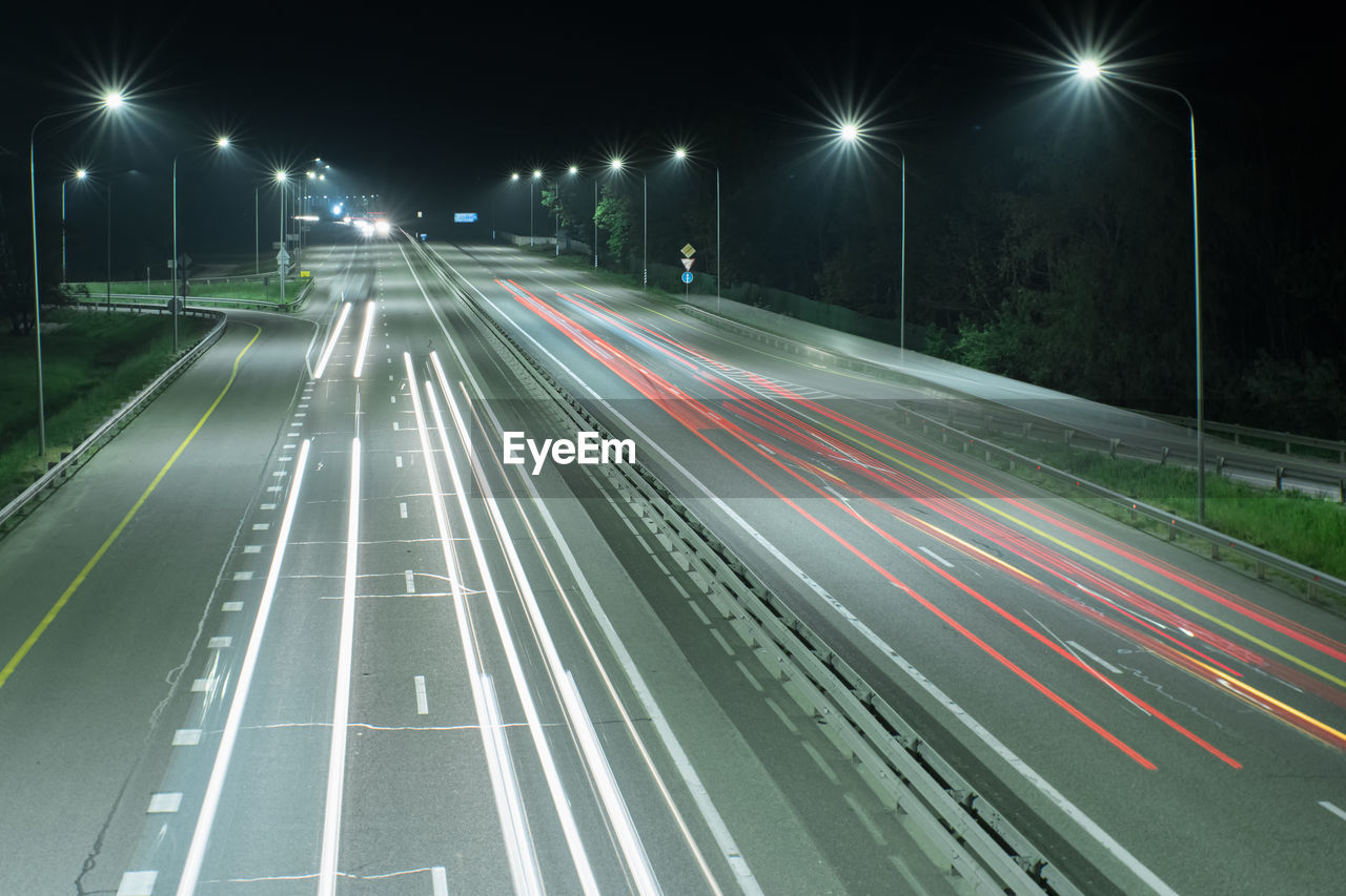BLURRED MOTION OF LIGHT TRAILS ON ROAD AT NIGHT