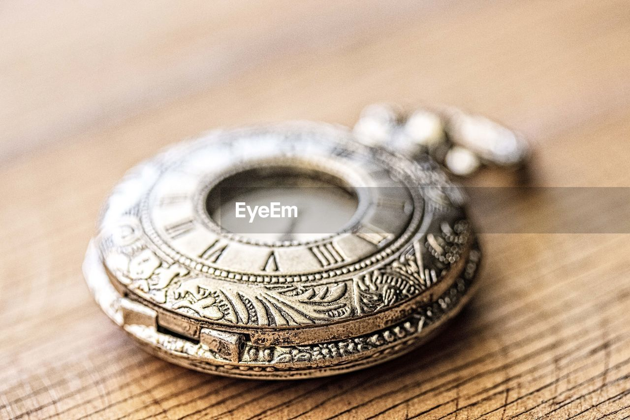still life, close-up, indoors, single object, no people, selective focus, table, wood - material, wealth, antique, focus on foreground, metal, studio shot, pattern, high angle view, two objects, design, finance, silver colored, jewelry, luxury, personal accessory