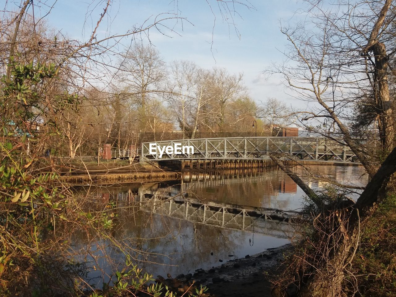 tree, water, built structure, architecture, day, bare tree, river, no people, outdoors, bridge - man made structure, sky, nature, building exterior, branch, beauty in nature