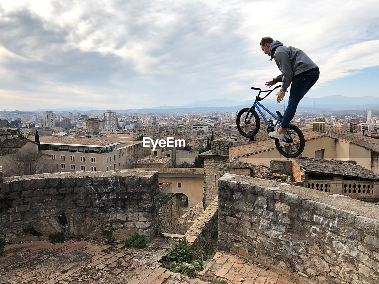 architecture, built structure, building exterior, stunt, one person, leisure activity, real people, lifestyles, skill, full length, sky, mid-air, nature, city, cloud - sky, bicycle, sport, young men, men, outdoors, riding
