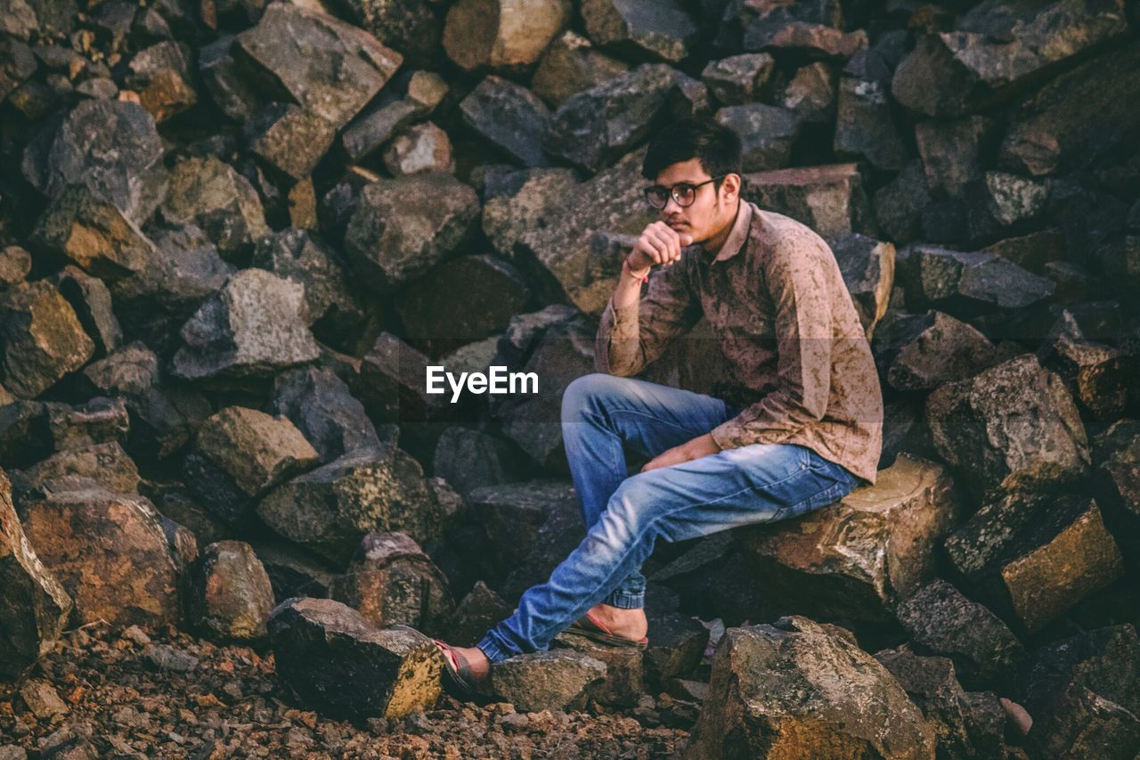 Thoughtful Young Man Looking Away While Sitting On Rock