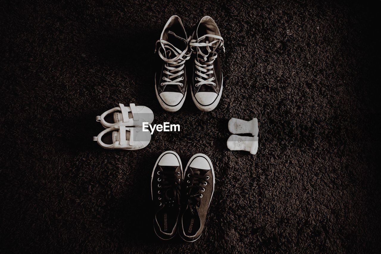 High angle view of shoes and baby booties on rug