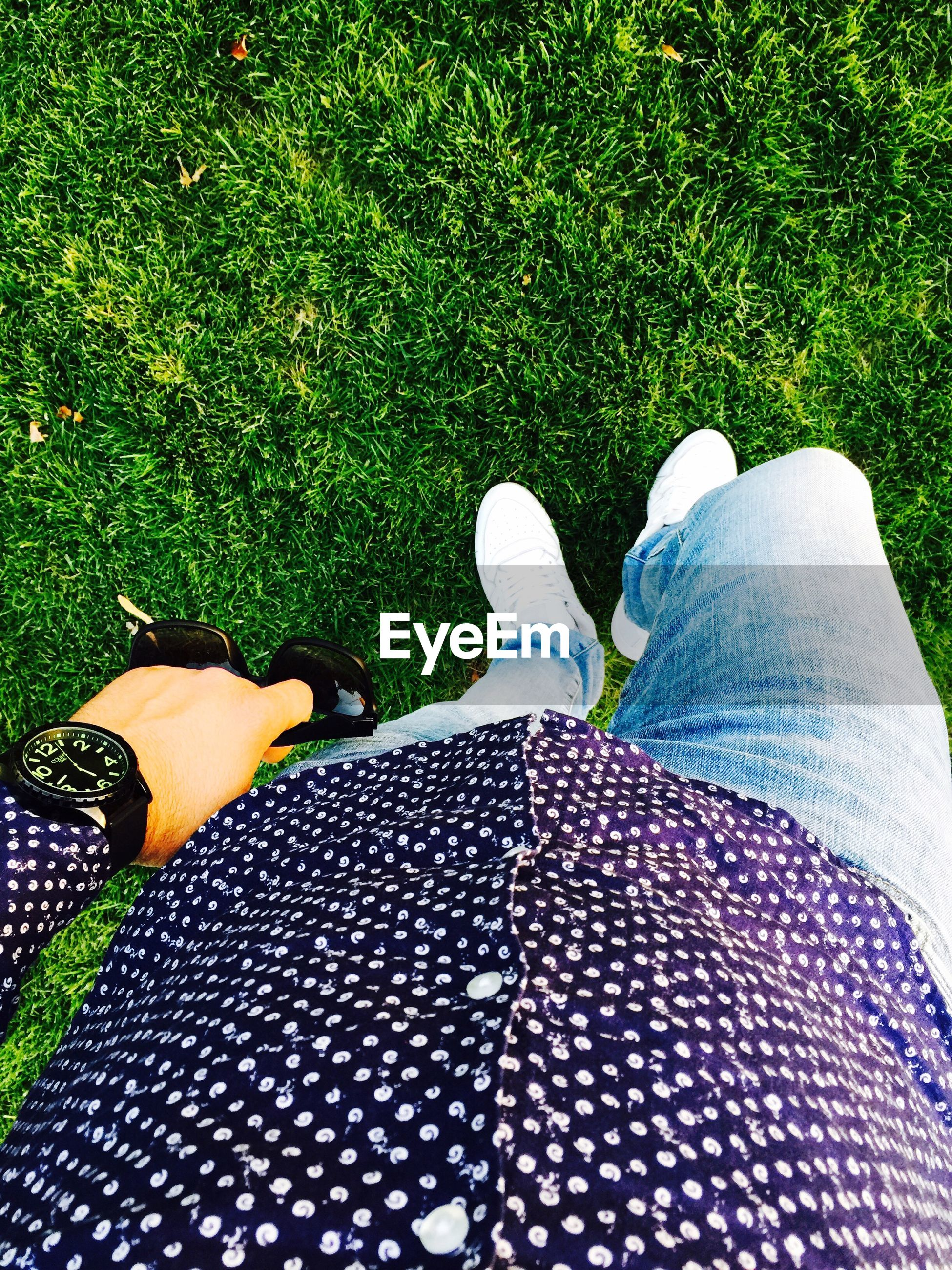 low section, person, grass, personal perspective, green color, high angle view, femininity, footwear, jeans, relaxation, grassy, close-up, field, casual clothing, day, blue