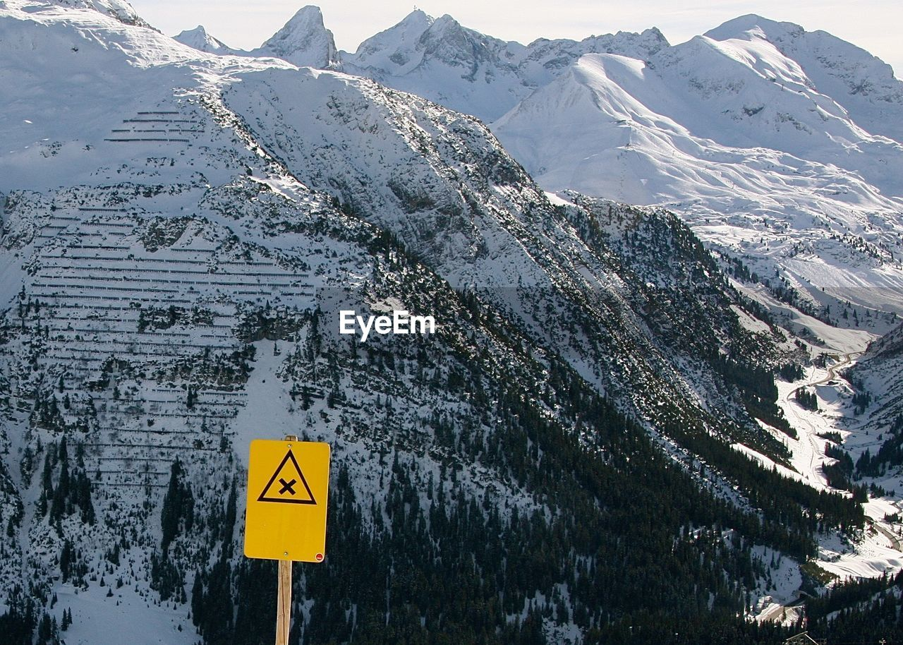 Warning Sign Against Snowcapped Mountains During Winter