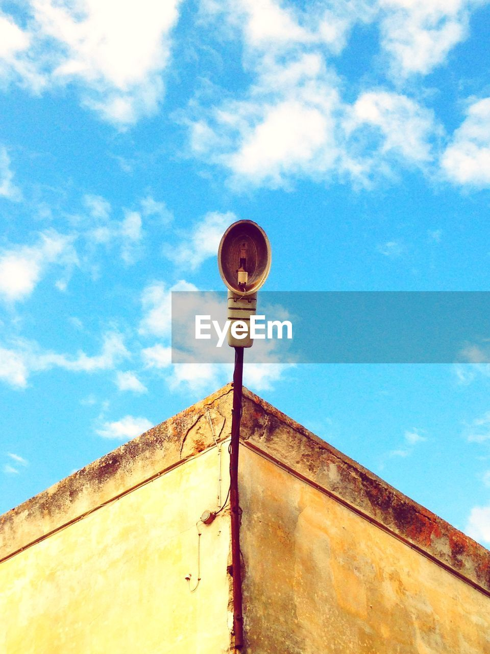 low angle view, sky, cloud - sky, built structure, day, architecture, nature, no people, blue, building exterior, outdoors, rusty, lighting equipment, metal, wall - building feature, wall, sunlight, security, protection, communication