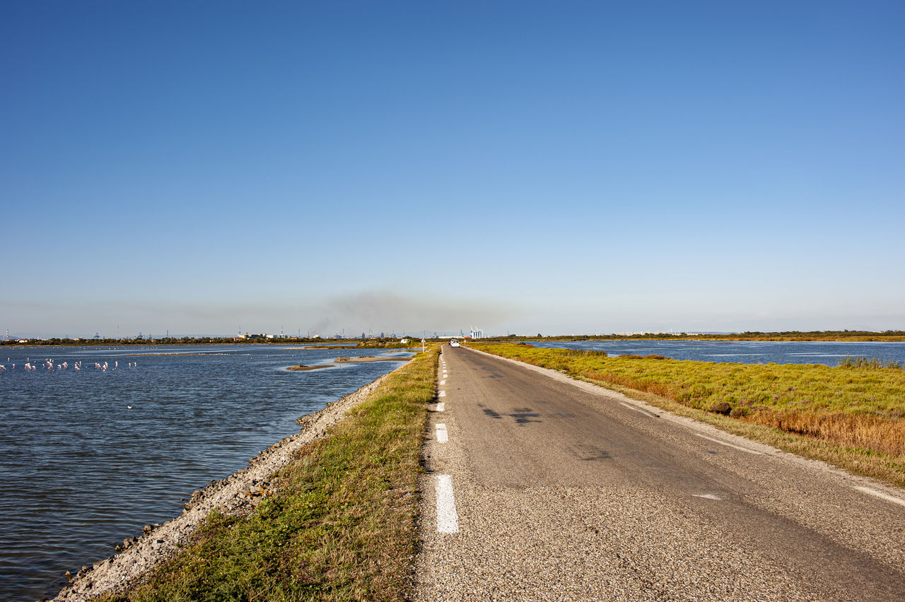 sky, water, copy space, tranquil scene, clear sky, scenics - nature, nature, tranquility, road, the way forward, direction, beauty in nature, day, no people, plant, transportation, diminishing perspective, grass, land, outdoors