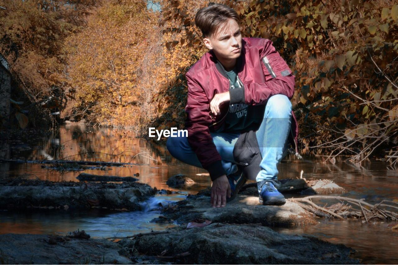 full length, crouching, autumn, one person, young adult, casual clothing, sitting, water, rock - object, young men, outdoors, nature, day, leaf, adult, tree, real people, only men, adults only, one man only, people
