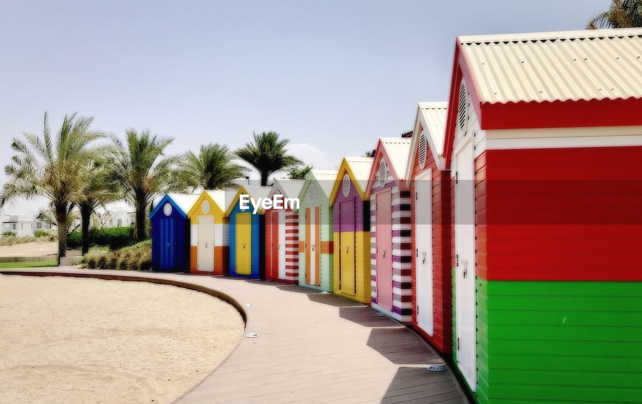 in a row, multi colored, day, clear sky, no people, built structure, outdoors, architecture, sky, tree