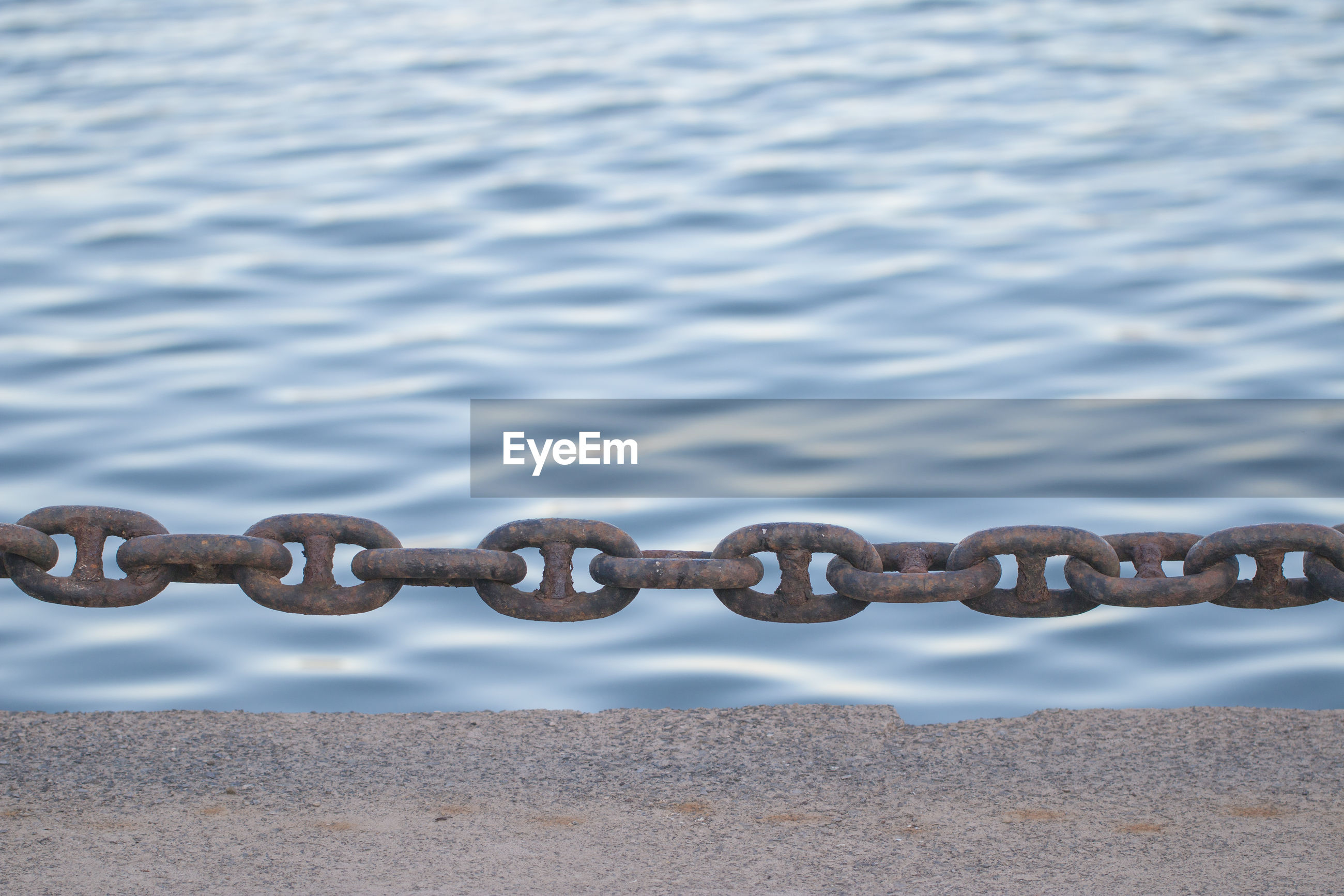 Close-up of rusty chain against river
