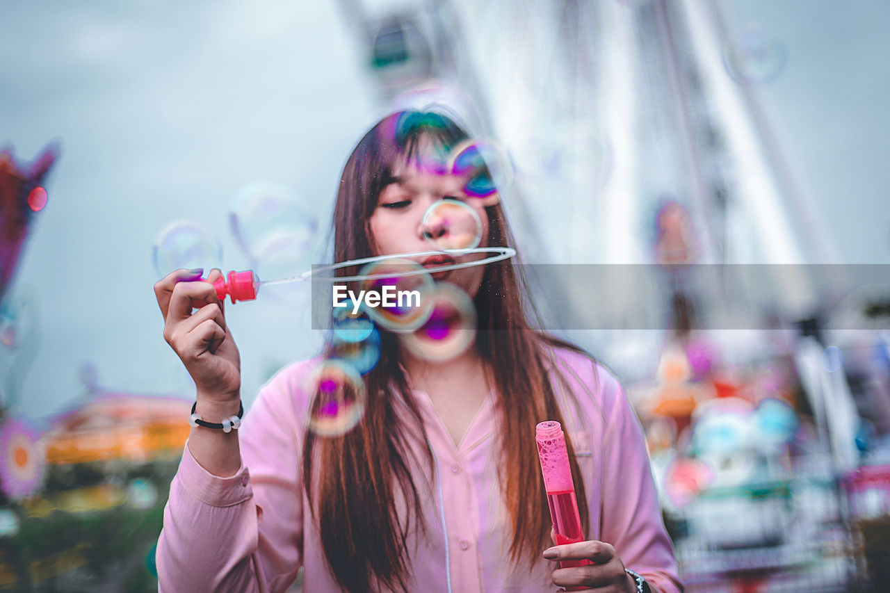 Woman blowing bubbles in city