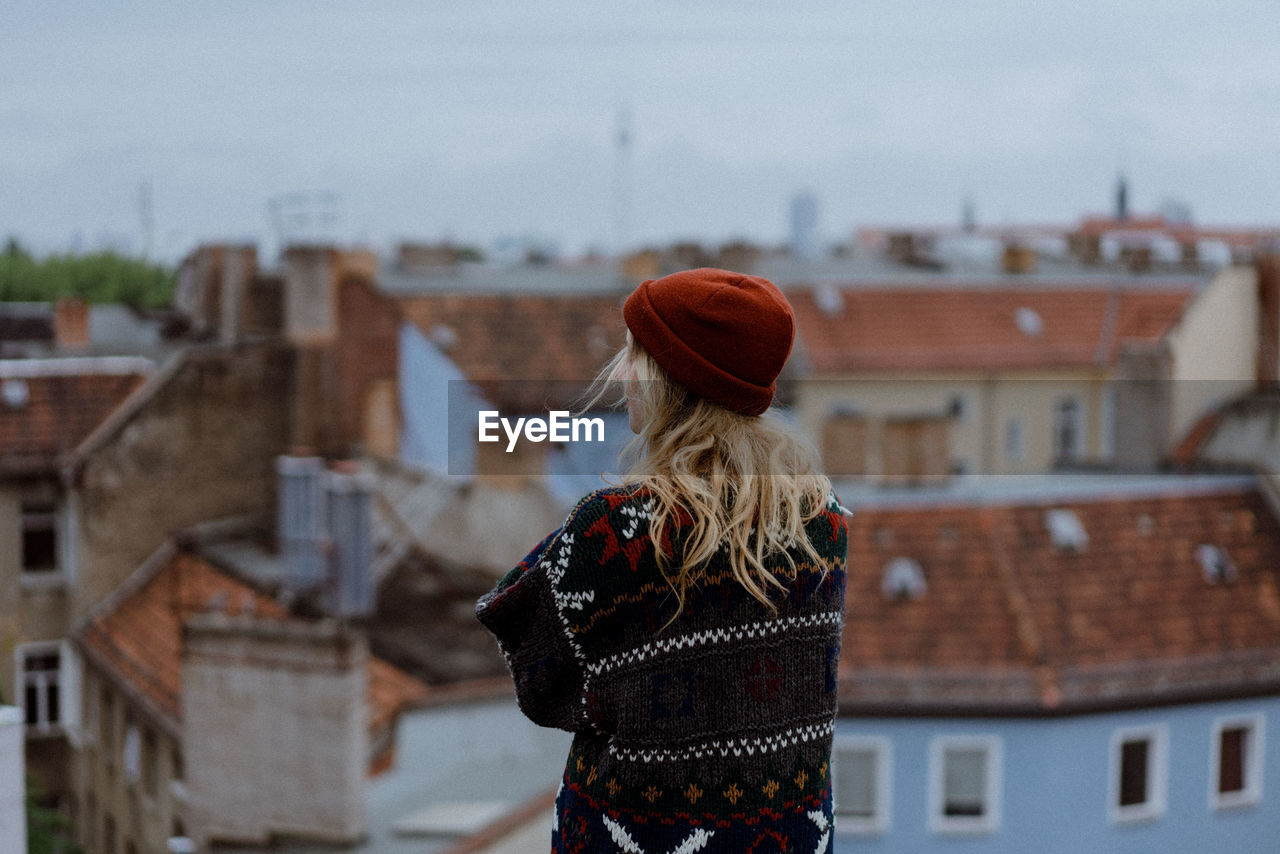 building exterior, architecture, built structure, one person, real people, rear view, lifestyles, building, women, focus on foreground, leisure activity, day, adult, city, standing, residential district, house, clothing, hair, warm clothing, outdoors, hairstyle, looking at view