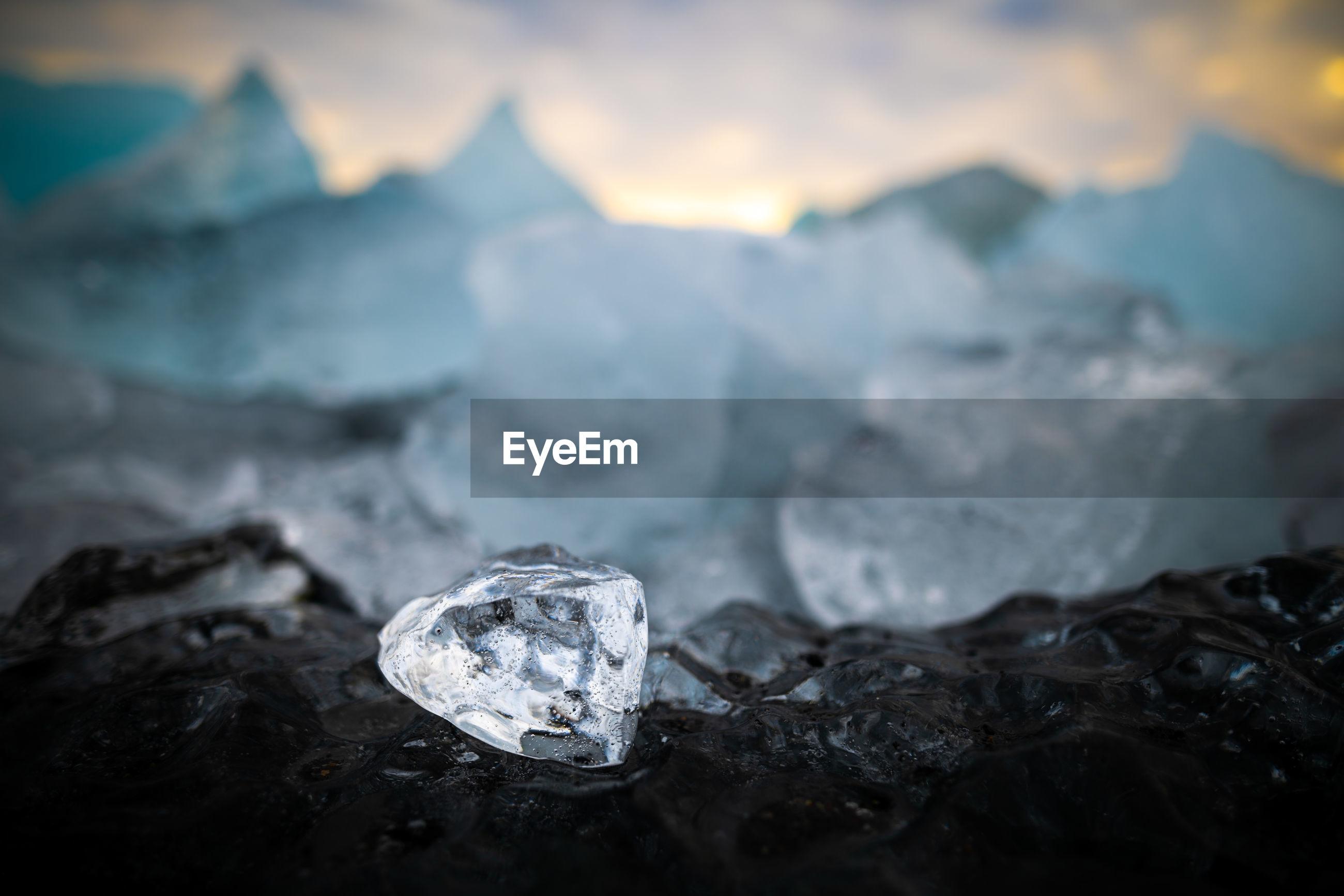 Ice cube on black ice at diamond beach near jokulsarlon glacier lagoon in iceland during sunset