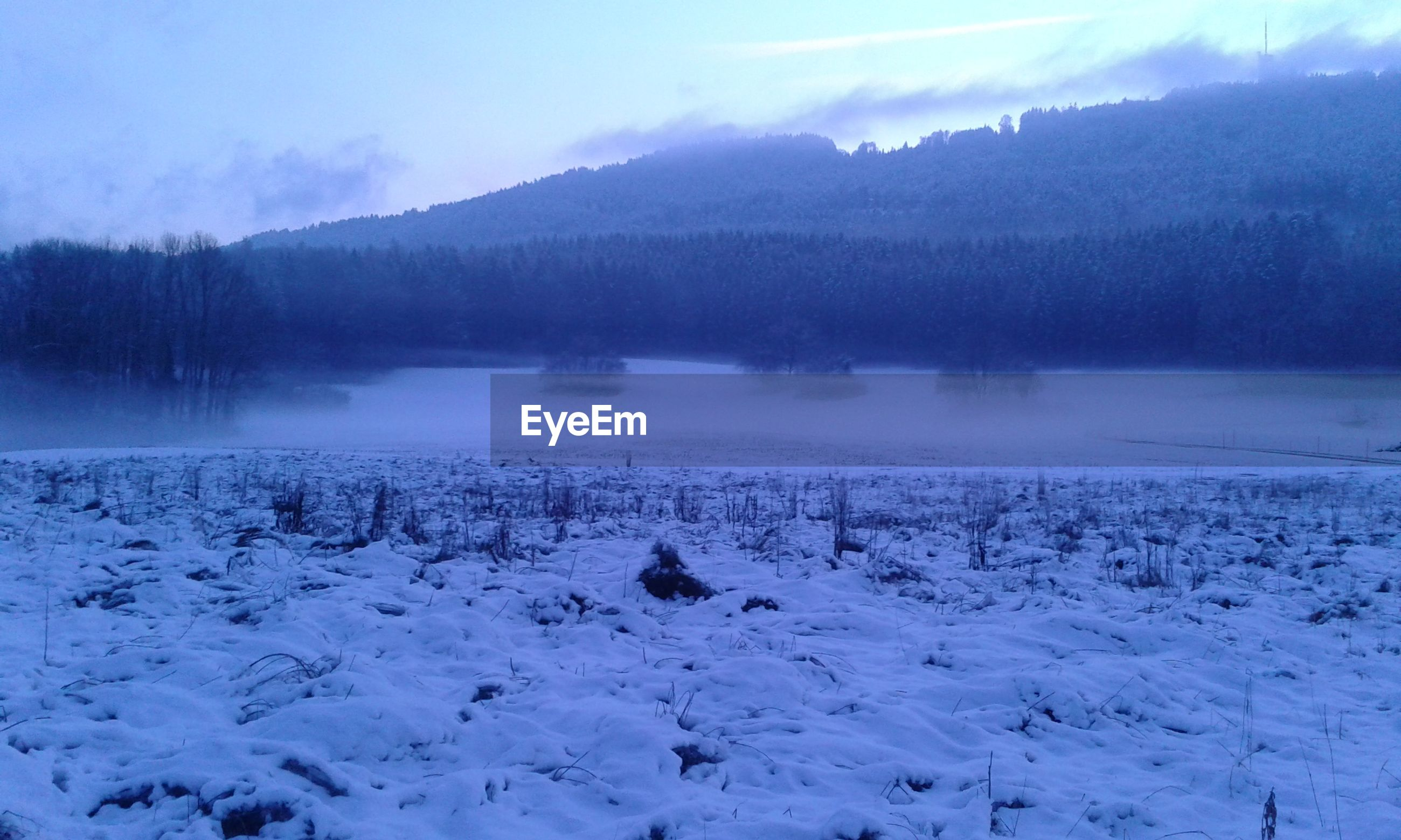 Scenic view of snow covered field by lake against sky