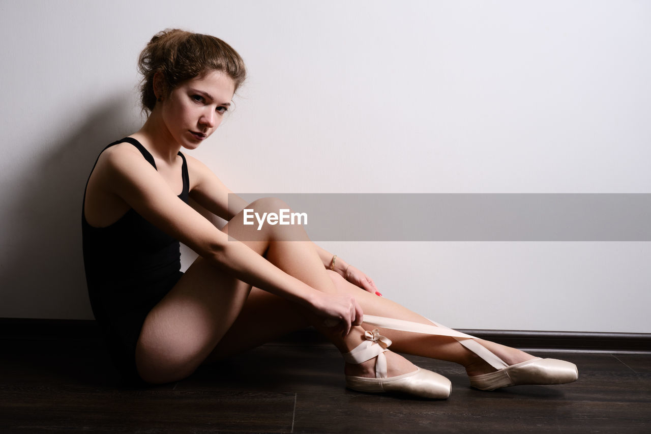 Young woman looking away while sitting on floor against wall